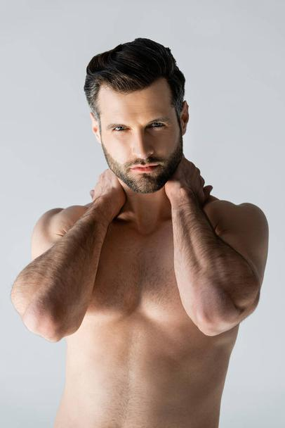 handsome and muscular man touching neck isolated on grey - Photo, Image