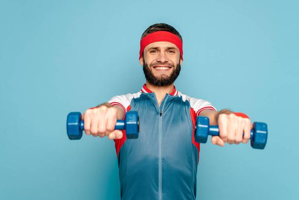 smiling stylish sportsman exercising with dumbbells on blue background - Photo, Image