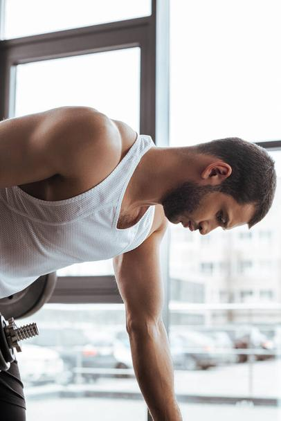 side view of athletic sportsman exercising near windows in gym   - Photo, Image
