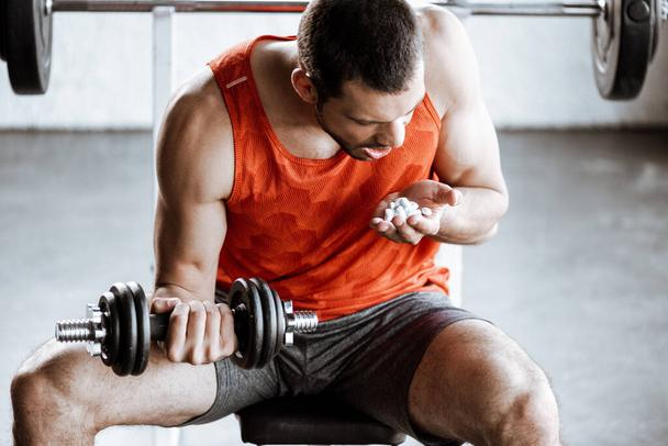 sportsman with opened mouth exercising with dumbbell and looking at probiotic pills in gym - Photo, Image
