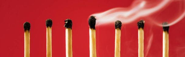 Unique burned match with smoke among another on red, panoramic shot - Photo, Image