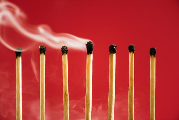 Unique burned match with smoke among another on red - Photo, Image