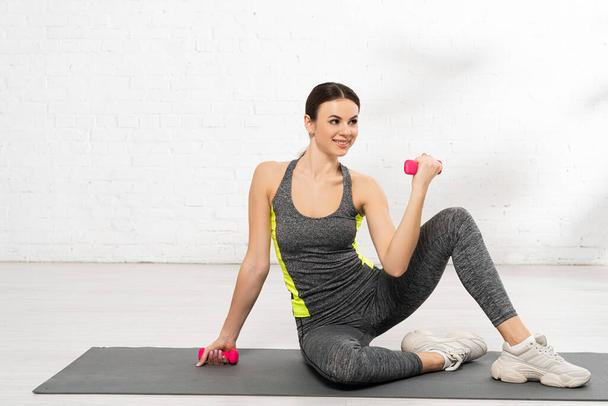 happy young sportswoman exercising with pink dumbbells on fitness mat - Photo, Image