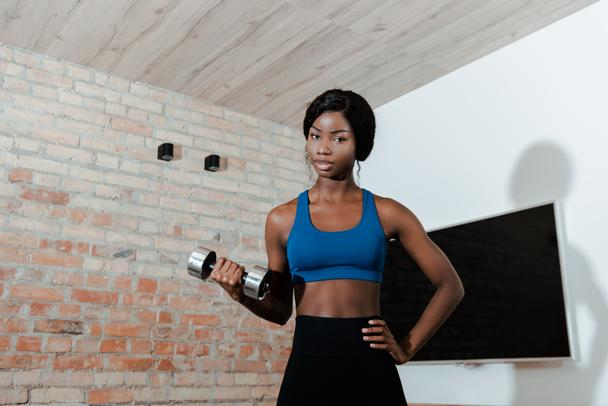 African american sportswoman with hand on hip training with dumbbell and looking at camera in living room - Photo, Image
