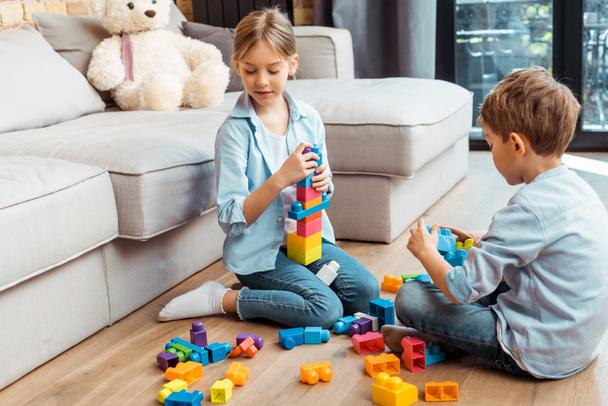 cute siblings playing with building blocks while sitting on floor in living room  - Photo, Image