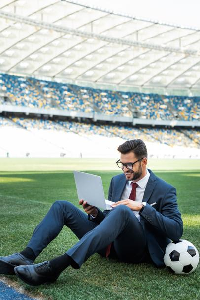 smiling young businessman in suit with laptop and soccer ball sitting on football pitch at stadium, sports betting concept - Photo, Image