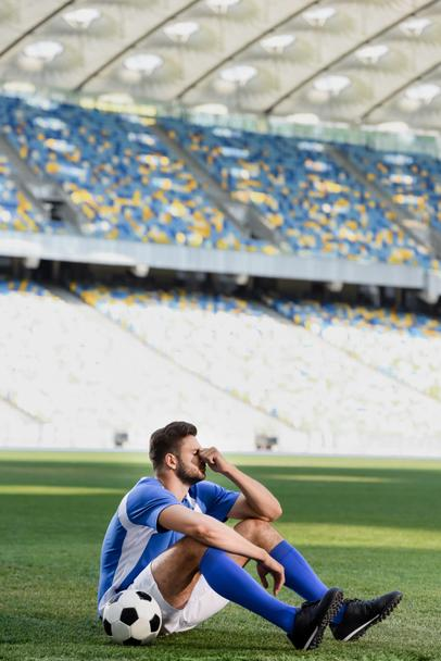 sad professional soccer player in blue and white uniform sitting with ball on football pitch at stadium - Photo, Image