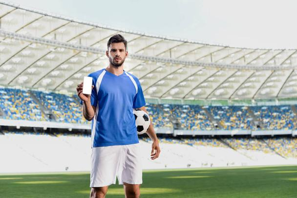 professional soccer player in blue and white uniform with ball showing smartphone with blank screen at stadium - Photo, Image