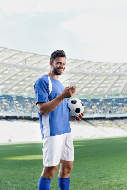 smiling professional soccer player in blue and white uniform with ball using smartphone at stadium - Photo, Image
