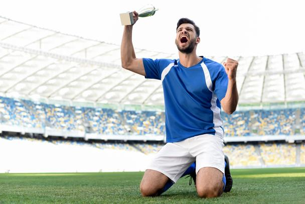 professional soccer player in blue and white uniform with sports cup standing on knees on football pitch and shouting at stadium - Photo, Image