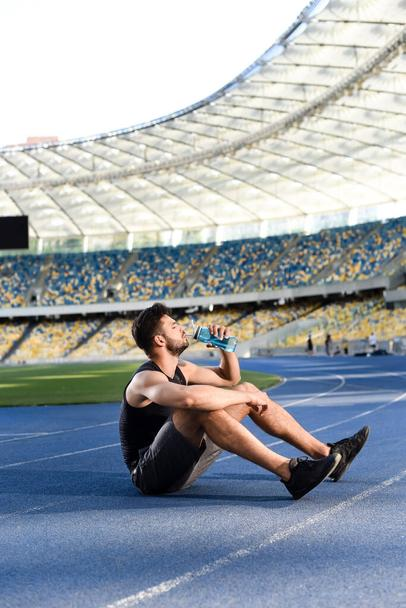 handsome sportsman resting and drinking water on running track at stadium - Photo, Image
