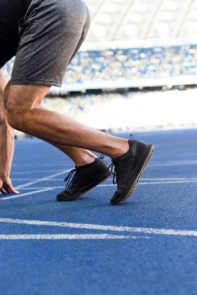 cropped view of runner in start position on running track at stadium - Photo, Image