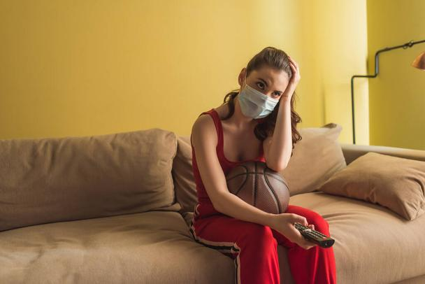 sportswoman in medical mask holding remote controller near basketball while watching championship in living room  - Photo, Image