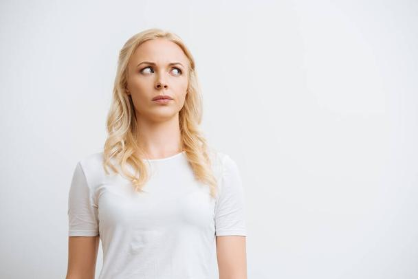 thoughtful blonde woman looking away while standing isolated on white - Photo, Image