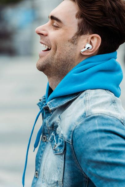 Side view of happy man in earphones laughing outdoors  - Photo, Image