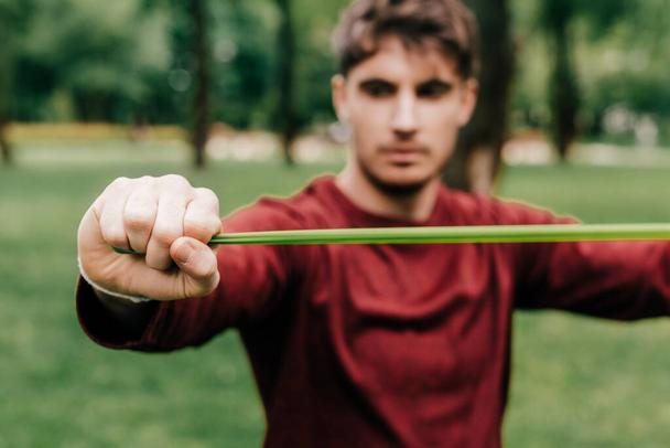 Selective focus of sportsman using elastics band while training in park  - Photo, Image