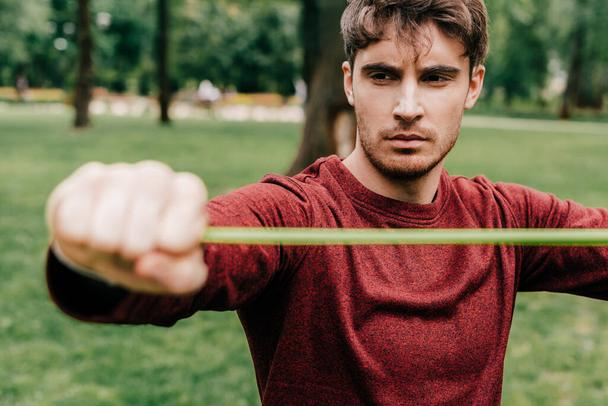 Selective focus of handsome man exercising with resistance band in park  - Photo, Image