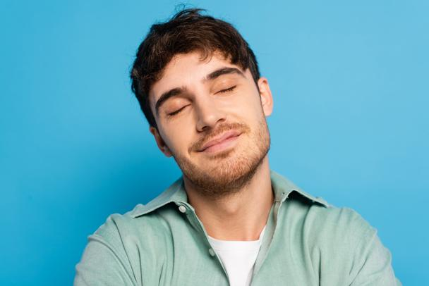pleased young man dreaming with closed eyes on blue - Photo, Image