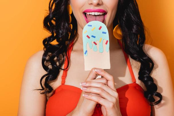cropped view of happy young woman licking paper cut ice cream on orange  - Photo, Image
