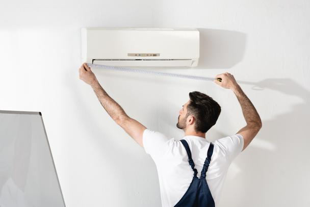 молодий ремонтник, що вимірює кондиціонер на білій стіні в офісі - Фото, зображення