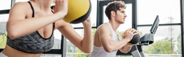 panoramic crop of sportswoman and sportsman exercising with balls in gym  - Photo, Image