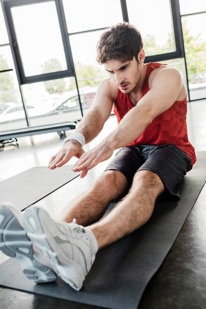 selective focus of handsome sportsman stretching on fitness mat  - Photo, Image