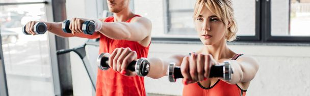 panoramic orientation of sport couple exercising with dumbbells in gym  - Photo, Image
