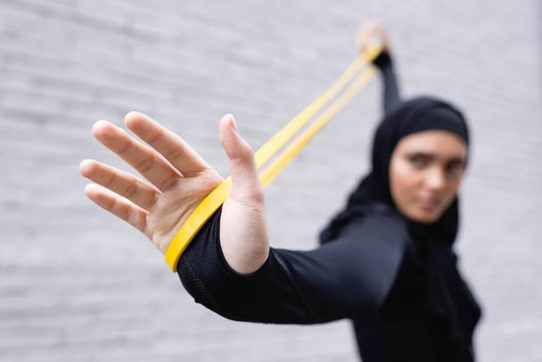 selective focus of arabian sportswoman in hijab exercising with resistance band near brick wall - Photo, Image