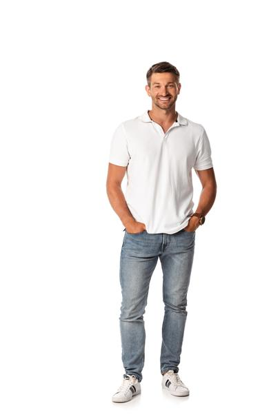 cheerful man in white t-shirt smiling while standing with hands in pockets on white  - Photo, Image