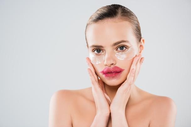 naked woman with lip mask and eye patches touching clean face isolated on grey - Photo, Image