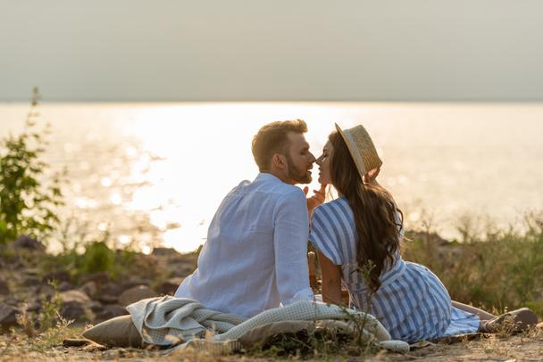 side view of handsome man and attractive woman in straw hat sitting near lake  - Photo, Image