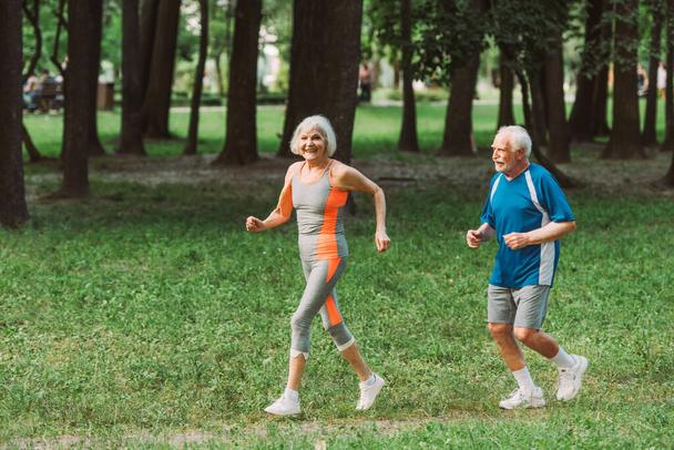Smiling senior woman looking at camera while jogging near husband in park  - Photo, Image