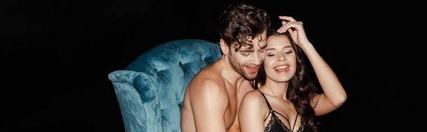 Horizontal image of shirtless man sitting near smiling woman in bra on armchair isolated on black  - Photo, Image