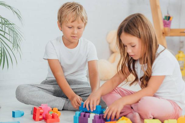 focused brother an sister in pajamas sitting on floor and playing with building blocks - Photo, Image