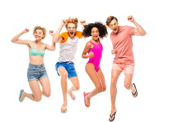 Multiethnic friends in sunglasses and swimsuits showing yeah gesture while jumping isolated on white - Photo, Image