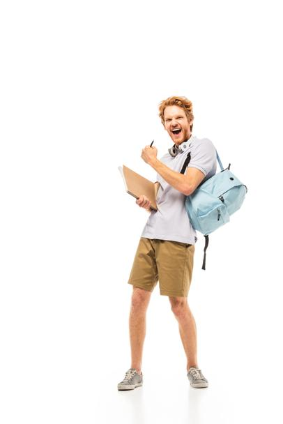 Student with backpack and notebook showing yeah gesture on white background - Photo, Image