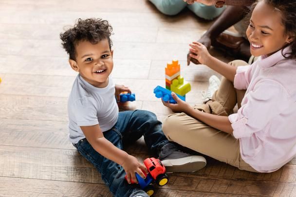 high angle view of african american brother and sister playing with toy truck and building blocks on floor at home - Photo, Image