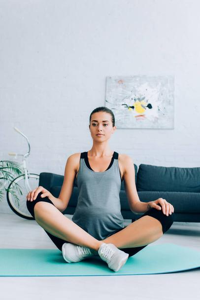 Pregnant sportswoman sitting with crossed legs in yoga pose on fitness mat at home  - Photo, Image