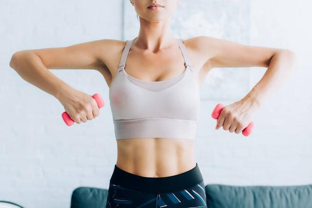 Cropped view of fit sportswoman holding dumbbells while exercising at home  - Photo, Image