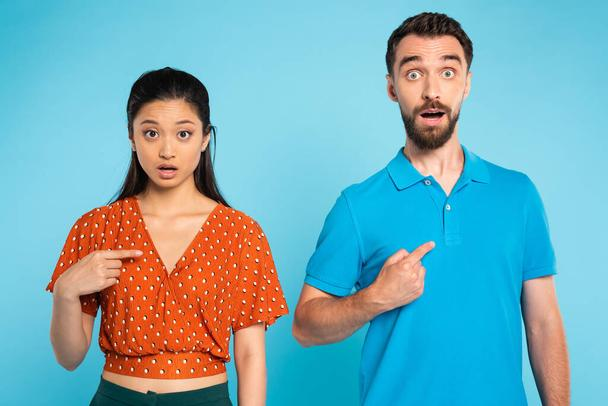 shocked asian woman in red blouse and bearded man in polo t-shirt pointing with fingers at themselves on blue - Photo, Image