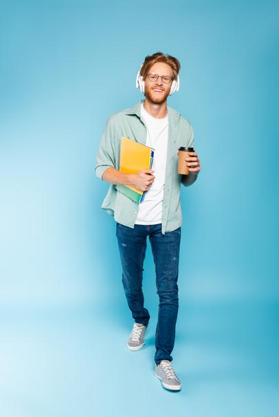 bearded student in glasses and wireless headphones holding paper cup and notebooks while walking on blue  - Photo, Image