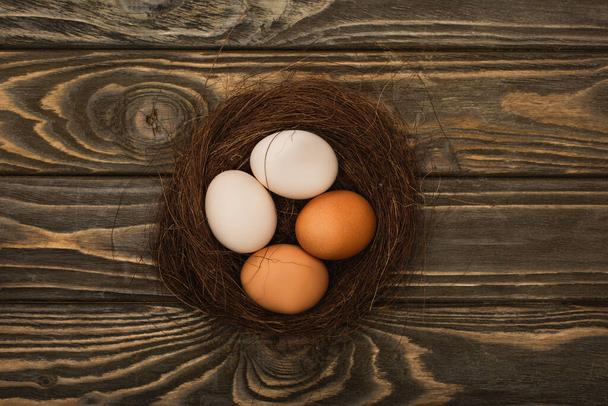 top view of fresh chicken eggs in nest on wooden surface - Photo, Image