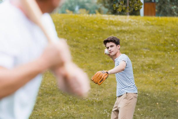 selective focus of teenager boy in leather glove holding ball while playing baseball with father - Photo, Image