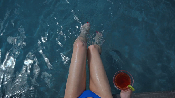 top view of wet woman in swimsuit sitting near pool with cocktail  - Footage, Video