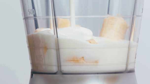 Close up of milk pouring into blender with bananas - Footage, Video
