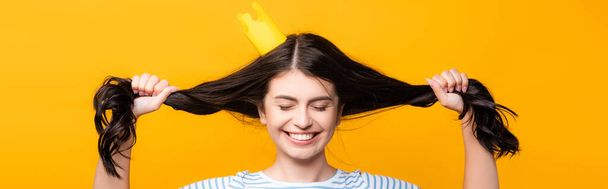 brunette woman in paper crown with closed eyes holding hair and smiling isolated on yellow, panoramic shot - Photo, Image