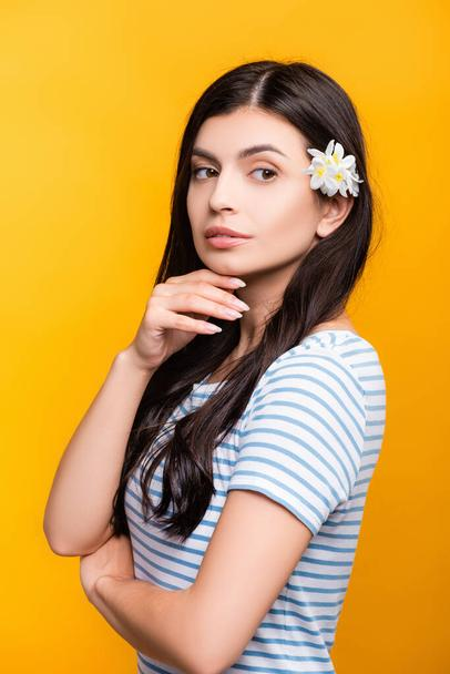 brunette young woman with flowers in hair looking away isolated on yellow - Photo, Image