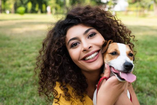Selective focus of joyful woman looking at camera and holding dog - Photo, Image
