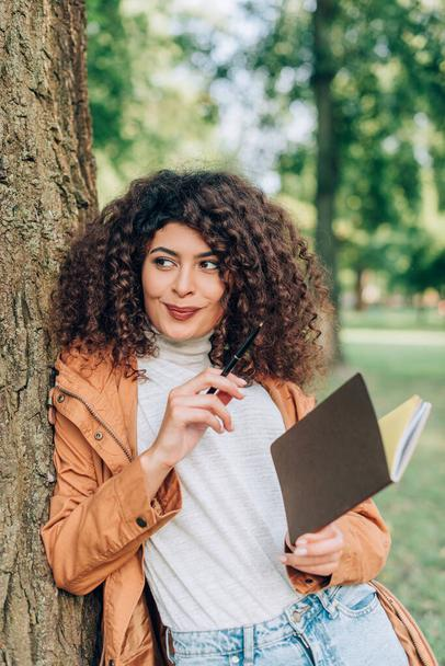 Selective focus of curly woman in raincoat looking away while holding pen and notebook in park  - Photo, Image