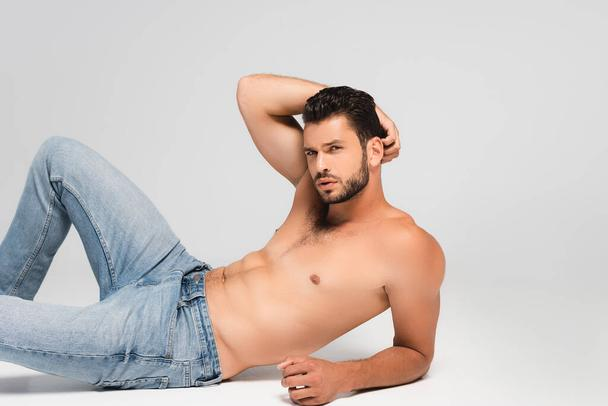sexy and bearded man in denim jeans lying on grey - Photo, Image